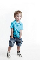 Studio shot of boy 6_7 with hands in pockets