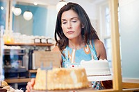 Woman looking on cake in cafe