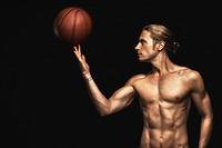 Profile of a handsome young man spinning a basketball on his finger