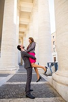 Couple under the colonnade of Saint Peter's cathedral Vatican Rome Italy