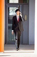Young Asian businessman walking and talking on his smartphone outside an office building