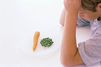 Boy with peas and carrot on a plate