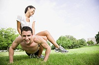 Man Doing Push_ups with His Girlfriend on His Back