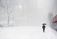 Pedestrian Walking Along Snowy Street