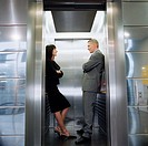 Businesswoman and Businessman Smiling at Each Other in Elevator