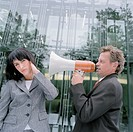 Businessman speaking into woman´s ear with megaphone