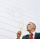 Businessman Blowing Large Bubbles