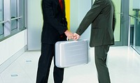 Two businessmen passing briefcase on corridor