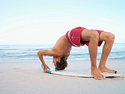 Young man doing a backbend on his surfboard