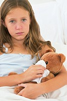 Sick girl holding teddy bear in bed