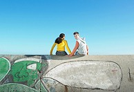 Teenage couple sitting on graffiti_covered wall