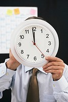 Businessman holding a clock in front of his face
