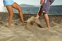 Couple kicking sand at each other