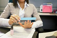 Businesswoman filing fingernails