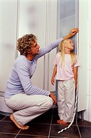 Father measuring size of his daughter with tape measure