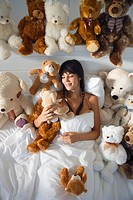 Woman Sitting in Bed Surrounded by Teddy Bears