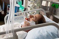 Patient in Hospital Bed Using Breathing Apparatus