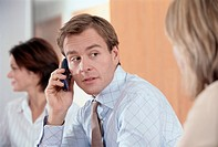 Businessman in Meeting Holding Cell Phone