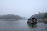 Early morning landscape of Periyar lake tourists on boat ride at Periyar lake , Periyar wildlife sanctuary , Thekkady , Kerala , India