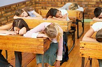 Schoolchildren asleep at their desks