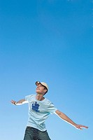 Teenage boy in T_shirt and baseball cap with arms outstretched
