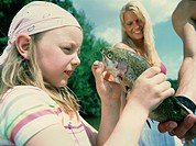 Girl looking at dead fish