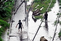 Children living in slums play in the flooded waters on the railway tracks caused due to heavy rains at Kurla Station , Bombay now Mumbai , Maharashtra...