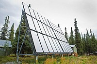 Solar water heating panels, spruce forest, at Denali Education Center, McKinley Village adjoining Denali National Park, Alaska, USA, late August