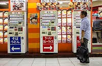Man choosing meal from vending machine at a noodle restaurant in Shinjuku station Tokyo city, Japan, Asia