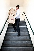 MODEL RELEASED. Carrying boxes. Office worker carrying boxes down stairs.