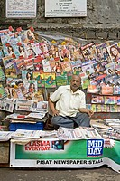 A newspaper vendor amidst his display of newspapers and magazines on the footpath ;  Mumbai Bombay ; Maharashtra ; India