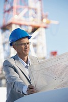 Building contractor holding blueprints