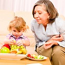 Grandmother with granddaughter eat fruit at home