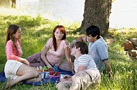 Two Young Couples Eating a Picnic in Woods