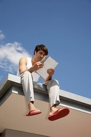 Young Man Reading Book on Rooftop