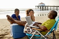 Man Using Laptop on Beach Watched by His Children
