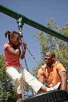 Father and daughter playing on tire swing