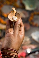 Woman holding diya in hand on Dev Diwali festival in Varanasi ; Uttar Pradesh ; India