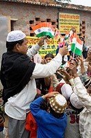Muslim man distributing Indian flag to school children on republic day 26th January in Varanasi ; Uttar Pradesh ; India