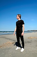 Young male in black clothes and white shoes standing on the beach