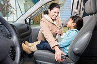 Mother fastening daughter´s seatbelt