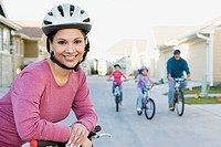 Woman riding bicycle with family