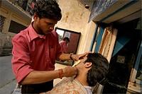A Young man getting his beard shaved at  Taj hair and beauty saloon  ; Dehradun ; Uttaranchal ; India
