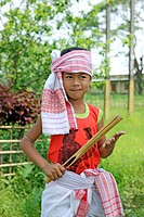 Boy playing a musical instrument and celebrating Bihu festival new year celebration Assam , India NO MR