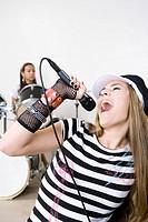 Teen girl singing in band