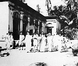 Mahatma Gandhi ; walking with Abha Gandhi ; Sushila Nayar ; Sushila Pai and others in front of a building in the area effected by Hindu Muslim riots i...