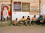 People reading daily newspapers seating on water pipes ; Bombay now Mumbai ; Maharashtra ; India