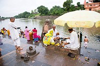Devotees performing religious ceremony on bank of holy river Narmada , Ujjain , Madhya Pradesh , India
