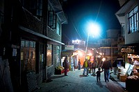 Street scene ; people walking in the light of Electric bulbs ; Jogibara road ; Mcleod Ganj ; Himachal Pradesh ; India