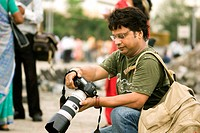 One professional photographer with digital SLR camera with big telephoto zoom lens busy to shoot Taj Mahal hotel , Bombay Mumbai , Maharashtra , India...